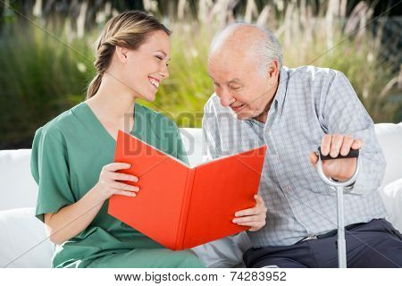 Smiling female nurse looking at senior man while reading book in nursing home