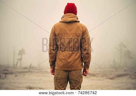 Young Man standing alone outdoor with foggy scandinavian nature on background