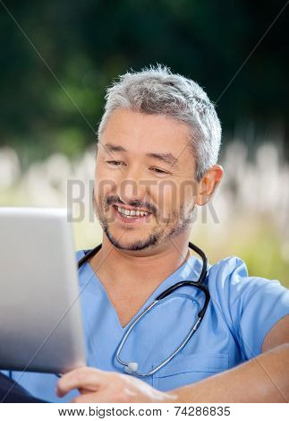 Male caretaker smiling while looking at tablet computer at nursing home porch