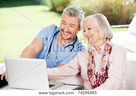 Happy caretaker and senior woman using laptop at nursing home porch