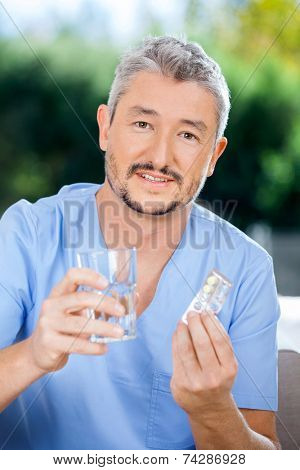 Portrait of male nurse caretaker holding blister pack and glass of water at nursing home porch