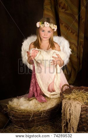 Pink little girl playing an angel in a Christmas nativity scene with a doll