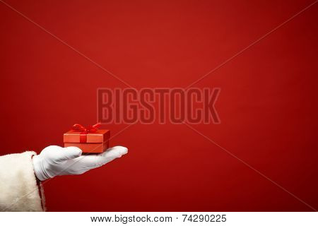 Santa Claus hand in white glove holding small red giftbox in isolation
