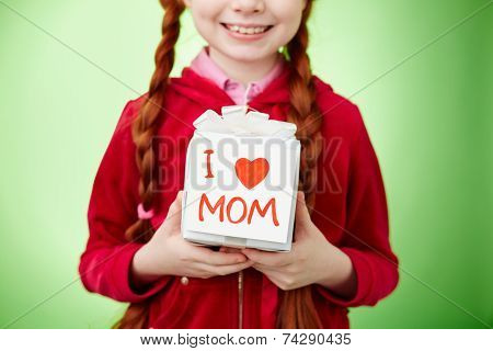 Giftbox with surprise for mother held by smiling girl