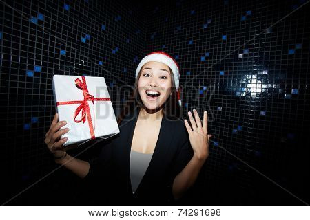 Ecstatic businesswoman in Santa cap holding Christmas present