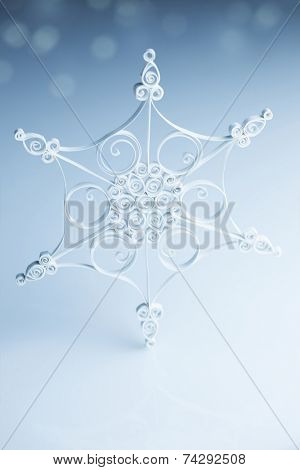 Beautiful handmade paper quilling snowflake on blue white background - vertical