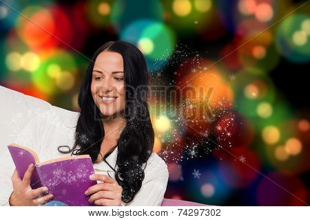 Smiling woman reading a book against blurred lights