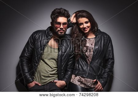Young fashion couple leanin on a grey wall while looking at the camera.