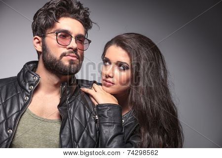 Beautiful woman resting on her lover shoulder looking at him, while he is looking away.
