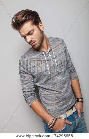Young fashion man looking down while holding his hands in pocket. on grey studio background.
