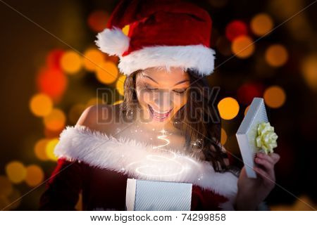 Sexy santa girl opening gift against close up of christmas lights