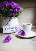 picture of vase flowers  - Cup of coffee and aster flowers in a vase on the wooden table