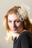stock photo of fascinator  - Redhead in cream fascinator and black top - JPG