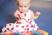 baby girl playing toy xylophone poster