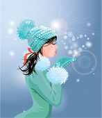 stock photo of blowing  - Beautiful brunette girl with warm blue winter hat is blowing snow from her hands  - JPG
