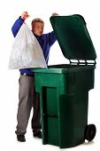 foto of dumpster  - A mature man dumping the household trash in a green dumpster - JPG