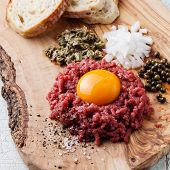 picture of tartar  - Beef tartare with capers and fresh onion on olive wood board - JPG