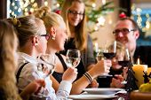 stock photo of wieners  - German parents and children toasting with wine and water at Christmas eve dinner  - JPG