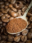 picture of coffee grounds  - Ground coffee on a silver spoon on coffee beans - JPG