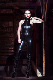 image of latex woman  - Sexy woman in latex outfit and handcuffs posing in the dark on the timber - JPG