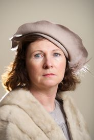 image of taupe  - Brunette in taupe hat and fur stole