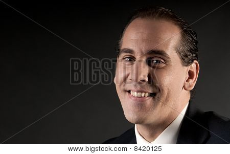 Adult Businessman Closeup Portrait Smiling On Dark Background.