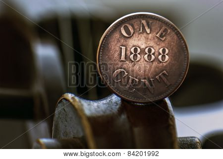 Old One Cent Coin On A Violin Scroll