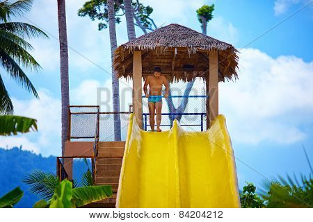 Man Having Fun On Water Slide In Tropical Aqua Park