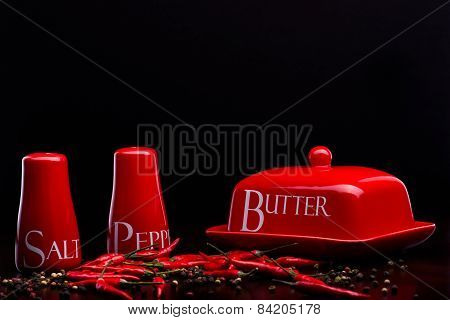 Red Salt-cellar, Pepper-box And Butter On Darck Background By Cristina Arpentina
