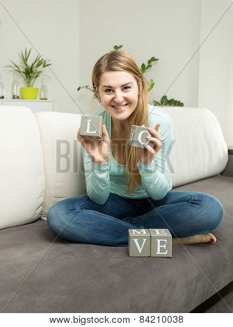 Woman Holding Bricks With Letters Making Word