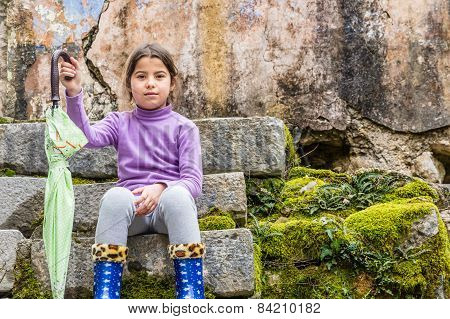 Seven Year Old Girl Sitting In The Park And Holding The Umbrella In Her Hand