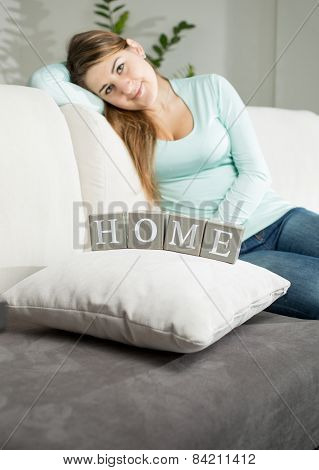 Woman Sitting On Sofa And Looking On Word