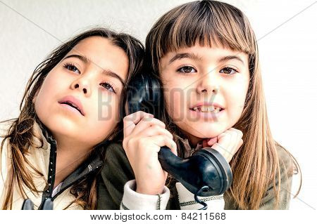 Seven Year Old Girl Talking On The Old Vintage Phone And Her Sister Eavesdropping Her Conversation.