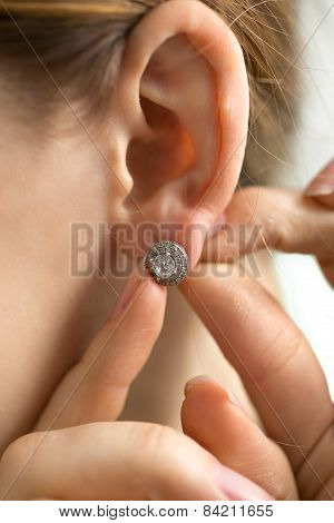 Macro Shot Of Young Woman Trying On Diamond Earring