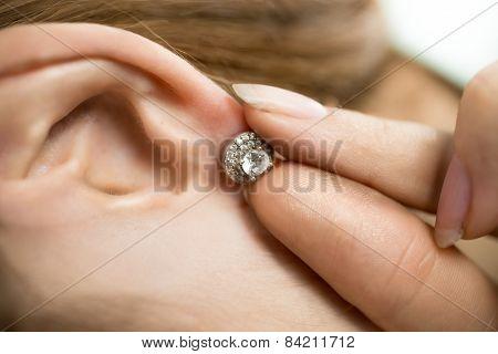 Closeup Shot Of Woman Putting Earring With Diamonds