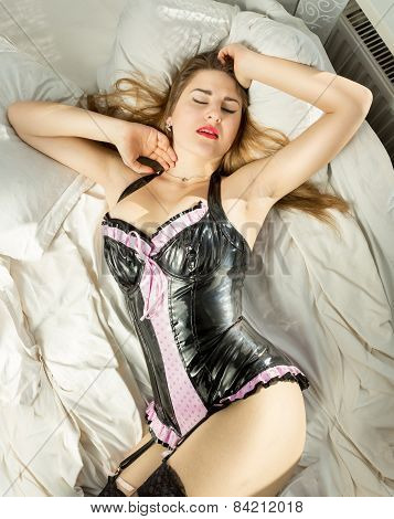 Sexy Woman In Latex Corset Lying In Bed