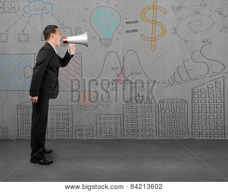 Businessman Using Megaphone Yelling With Business Concept Doodles Wall
