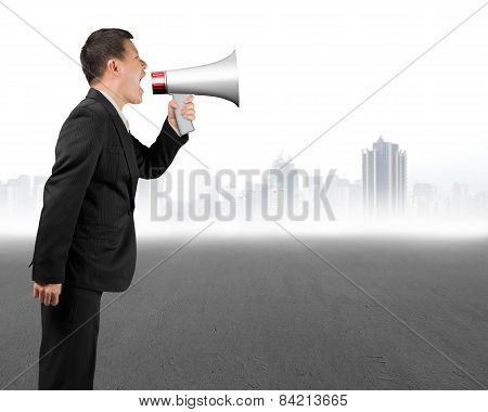 Business Man Using Megaphone Yelling With Gray Cityscape