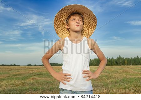 Portrait Of Farmer Boy On Harvested Field