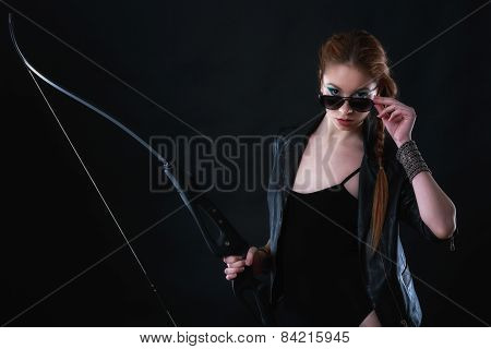 beautiful woman with bow in hand on black background