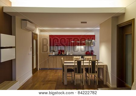 Living room with kitchen site and dining-table in renovated apartment