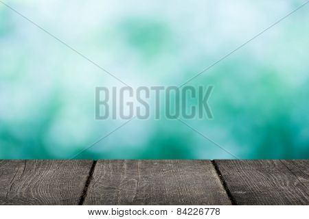 empty wooden table with blue bokeh background