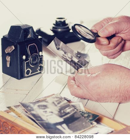Old man hands, view photos with magnifying glass from the past, retro cameras on the table, filtered