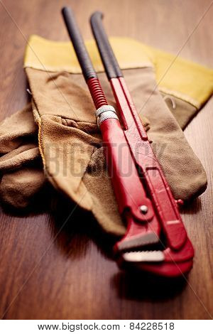 Pipe Wrench On Gloves Above The Wooden Table