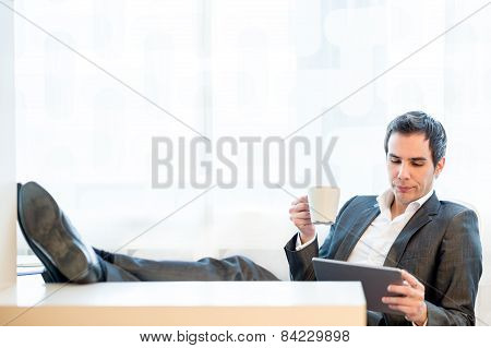 Businessman With His Feet On The Desk Enjoying A Cup Of Coffee