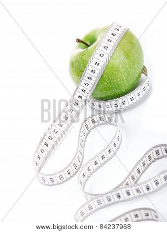 Green Shiny Apple, Wrapped With A White Measuring Tape To Signify Dieting And Weight Loss