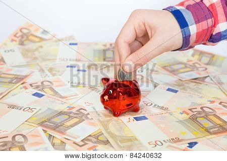 Hand putting euro coin in red piggy bank