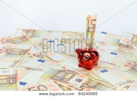 Small red piggy bank on many euro notes