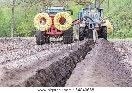 Two agriculture tractors digging drainage pipes in ground