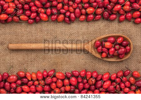 Wooden Spoon With Rosehip  Lies On  Sackcloth